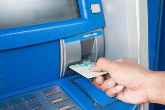 Mann mit Geldautomaten mit seiner Kreditkarte