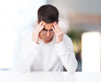 Mann mit Kopfschmerzen mit den Händen auf Tempel