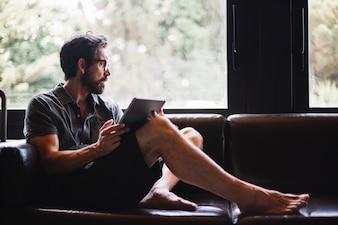 Mann mit Tablet aus dem Fenster