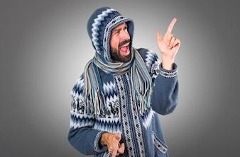 Mann mit Winterkleidung tanzen auf grauem Hintergrund