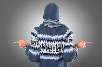 Mann mit Winterkleidung zeigt auf die Seiten mit Zweifeln auf grauem Hintergrund