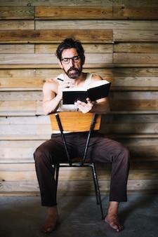 Mann mittleren Alters, der in Buch schreibt