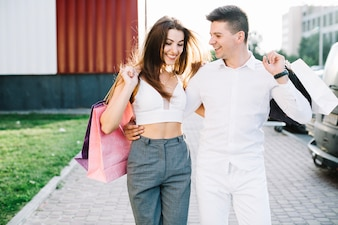 Mann umarmt seine Freundin, die Straße hinunter