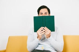 Mann versteckt sich hinter einem Buch