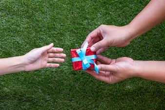 Männliche und weibliche Hände mit roter Geschenkbox mit Schleife