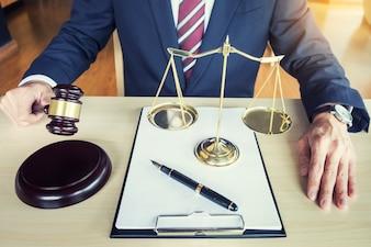 Männlicher Richter in einem Gerichtssaal, der den Hammer auf Klangblock schlägt
