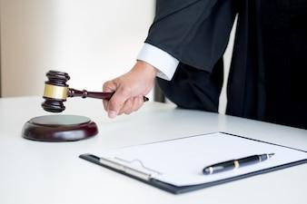 Männlicher Richteranwalt in einem Gerichtssaal, der den Hammer auf klingenden Block schlägt