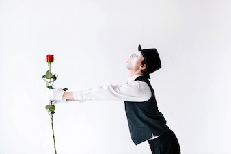 Mime streckt seine Hände mit roter Rose aus