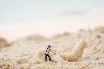 Miniatur-Ingenieur der Bauarbeiter mit Koralle. Vintagen Ton. Retro-Filter-Effekt, Soft-Fokus, schwaches Licht (selektiven Fokus)
