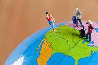 Miniatur-Menschen auf dem Globus unterwegs