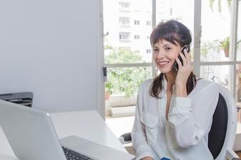 Moderne Frau am Schreibtisch mit Laptop und Telefon