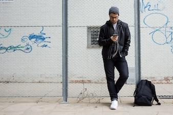 Moderner junger Mann, der Musik mit Handy auf der Straße hört.