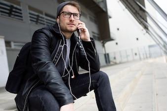 Moderner junger Mann, der Musik mit Kopfhörern auf der Straße hört.
