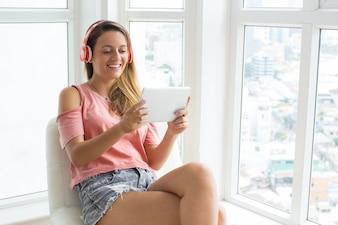 Modernes Mädchen mit Gadget für Unterhaltung