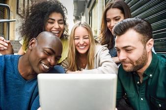Multi-ethnischen Gruppe von jungen Menschen Blick auf einen Tablet-Computer