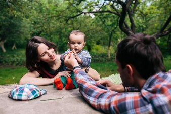 Mutter und Vater füttern Kinder draußen