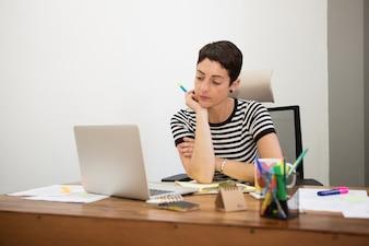 Nachdenkliche Geschäftsfrau auf ihrem Laptop