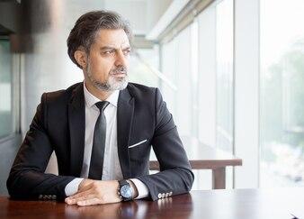 Nachdenklicher Unternehmer sitzt am leeren Schreibtisch