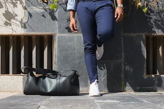 Nahaufnahme der Mann-Beine und Ledertasche