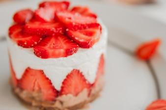 Nahaufnahme von Erdbeerkuchen mit frischen Erdbeeren auf Holzuntergrund. Hausgemachte Erdbeerkuchen. Käsekuchen mit Erdbeere