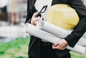 Nahaufnahme von Frau Ingenieur mit gelben Helm in der Hand gegen Stadt Bau Hintergrund