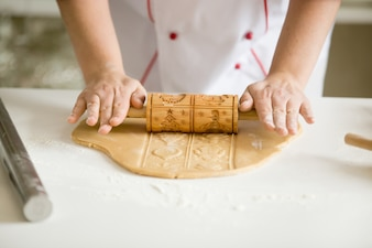 Nahaufnahme von Händen rollen Lebkuchen Teig mit gemusterten rolle
