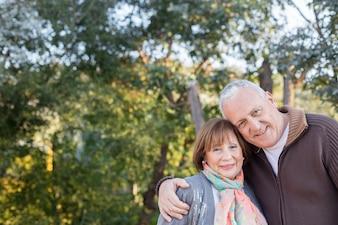 Nahaufnahme von Senior Paar umarmt mit Bäumen Hintergrund