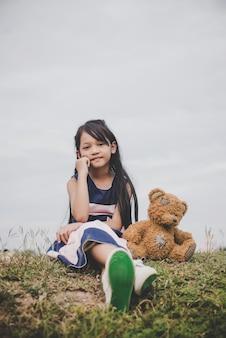 Nette asiatische Mädchen mit Teddybär sitzt auf Wiesen Feld. Freundschaftskonzept.