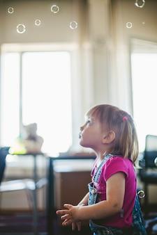 Nettes Mädchen stehend Blick auf Seifenblasen