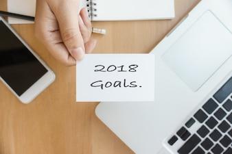 Neujahr 2018 - Nahaufnahme Draufsicht Foto Frau zeigt 2018 Tor Liste auf Visitenkarte und mit modernen Laptop und Handy auf Holztisch verschwommen Hintergrund.