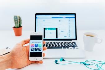 Nützliche Apps am Telefon und moderner Schreibtisch mit Laptop