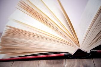 Offenes Buch auf Holztisch.
