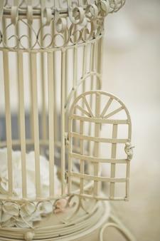 Öffnen Sie die Tür des weißen Vogelkäfigs