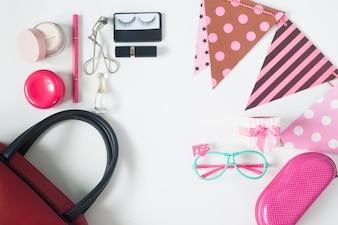 Overhead Blick auf wesentliche Schönheit Elemente, Top Blick auf Party Zubehör, rote Handtasche, Mode Brillen und Kosmetik, Draufsicht isoliert auf weißem Hintergrund