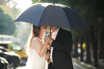 Paar unter Regenschirm küssen