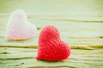 Paar von Häkeln Herzen in rot und rosa über Holz Hintergrund. Foto ist auf das rote Herz fokussiert.