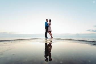 Paare auf einem Strand umarmen