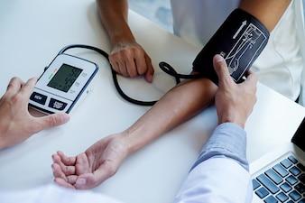 Patient hört aufmerksam auf einen männlichen Arzt, der Patientensymptome erklärt oder eine Frage stellt, wenn er in einer Konsultation zusammen Papierkram bespricht