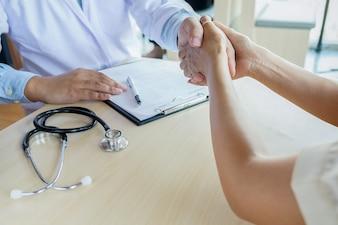 Patient hört aufmerksam zu einem männlichen Arzt, der Patienten Symptome erklärt oder eine Frage, wie sie diskutieren Papierkram zusammen in einer Konsultation