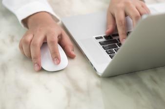 Person schriftlich mit einer Hand und die andere eine Maus berühren