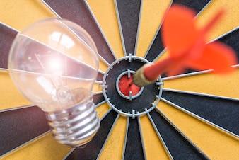 Pfeil schlägt das Bullseye Ziel mit Ideenlampe auf Dartscheibe