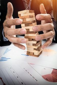 Planung, Risiko und Strategie in Business-Konzept, Geschäftsmann Glücksspiel Platzierung Holz-Block auf einem Turm.