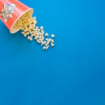 Popcorn auf blauem Hintergrund mit Platz auf der rechten Seite