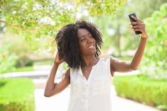 Portrait der fröhlichen Frau, die selfie im Park nimmt