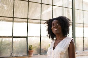 Portrait der glücklichen jungen Frau Wegschauen drinnen