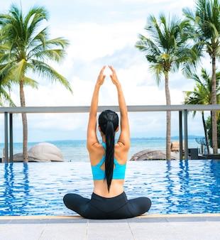 Porträt der jungen Frau (Fitness, Yoga, perfekt gebräunte Körper, gesunde Haut) im Luxus-Pool. Reisen und Urlaub. Freiheitskonzept. Außenaufnahme
