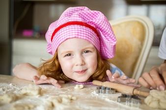Porträt von lächelnden kleinen Mädchen tragen Köche Hut