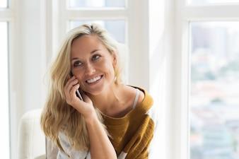 Positive junge Frau spricht auf Handy