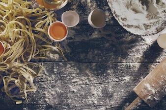 Prozess der Kochen Pasta mit rohen frischen Zutaten für klassische italienische Lebensmittel - rohe Eier, Mehl auf Holztisch. Draufsicht. Toning