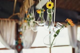 """""""Blumen in kleinen Vasen, die an Seilen hängen"""""""